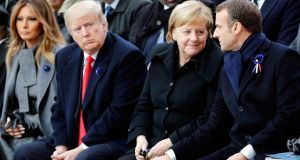 US first lady Melania Trump and US president Donald Trump look on as  German chancellor Angela Merkel talks to French president Emmanuel Macron at the Arc de Triomphe in Paris on November 11, 2018. Photograph:  François Mori
