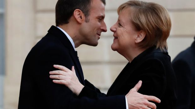 French president Emmanuel Macron hugs German chancellor Angela Merkel in Paris as the 100th anniversary of the end of first World War is marked. Photograph: Thibault Camus