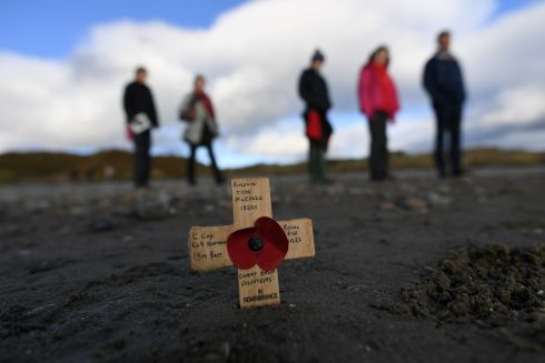 A remembrance cross is planted in the sand as volunteers draw depictions of those killed in the first World War, part of Danny Boyle's Pages of The Sea celebrations, on Murlough Beach in Newcastle, Northern Ireland. Photograph: Clodagh Kilcoyne/Reuters