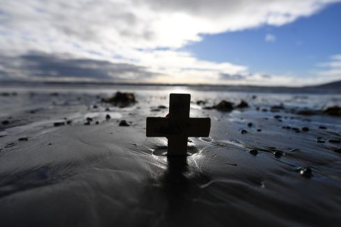 A remembrance cross is planted in the sand as volunteers draw depictions of those killed in the first World War, part of Danny Boyle's Pages of The Sea celebrations, on Murlough Beach in Newcastle, Co Down. Photograph: Clodagh Kilcoyne/Reuters