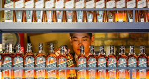 A bartender takes a bottle of Johnnie Walker whisky. Parent group Diageo is selling 19 spirits brands, including Seagrams VO whisky to US-based company Sazerac for $550 million. Photograph: Shamil Zhumatov