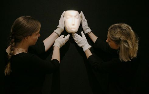 MOORE'S MASK: Staff at Bonhams auction house in London hold up a mask sculpture by Henry Moore before it is offered for auction. The work is one of 12 known, small carvings by Moore, titled Mask. It is the only one carved from alabaster, and is estimated to fetch £1 million to £1.5 million (€1.14 million-€1.71 million). Photograph: Jonathan Brady/PA Wire