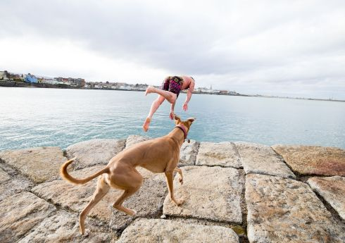Ian Cummins from Sallynoggin,Dublin  and his dog Sadie dive into the sea at Sandycove Beach. Photograph: Tom Honan