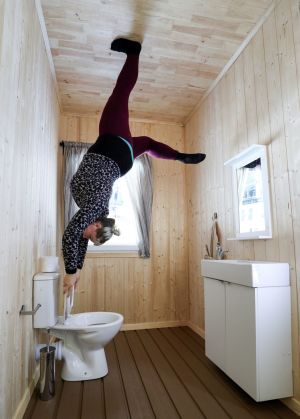 An employee holds on to the toilet seat in the bathroom in The Upside Down House, a zero-gravity illusion experience, in The Triangle in Bournemouth, Dorset. Photograph: Andrew Matthews/PA