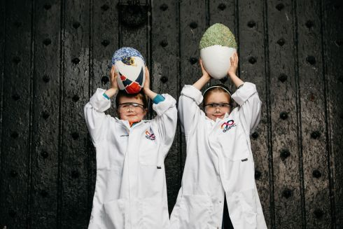 The Science Foundation Ireland Pharmaceutical Research Centre captures science demonstrations at a variety of locations for a campaign run in association with Science Week called #Sites4Science. Gus Sheehy, Tulla, Co Clare, and Grace Harper, Castletroy, Limerick, at the fantastic big black door to King John's Castle, Limerick, hold a rugby ball covered in crystals. Photograph: Sean Curtin