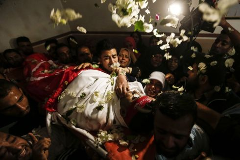 Relatives of Mohammed Ouda, killed in an Israeli air stike the previous day, throw flowers over his body during his funeral in Beit Lahia in the northern Gaza Strip. Photograph: Mahmud Hams/AFP/Getty Images