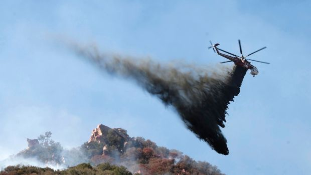A helicopter drops water on brush burning near Pepperdine University in an attempt to tackle the Woosley Fire in Malibu, California. Photograph: Mike Nelson/EPA