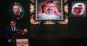 Yasin Aktay speaks in front of images of murdered journalist Jamal Khashoggi during a commemorative ceremony. Photograph: Chris McGrath/Getty Images