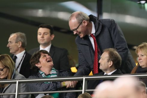 DUP leader Arlene Foster shakes hands with Tanaiste Simon Coveney as they attend the international soccer friendly between the Republic of Ireland and Northern Ireland at the Aviva stadium in Dublin. Photo: Brian Lawless/PA Wire