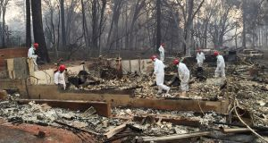 Volunteer rescue workers search for human remains in the rubble of homes burned in the Camp Fire in Paradise, California, on Thursday. Photograph: Terry Chea/AP