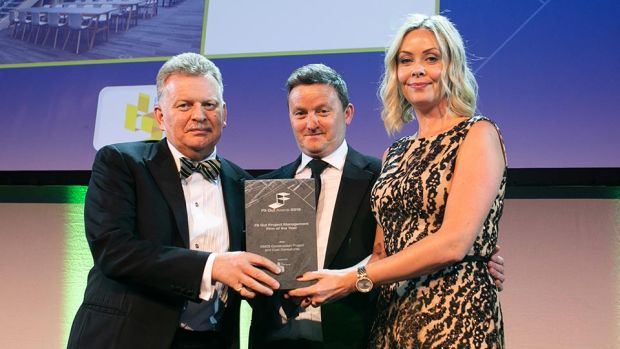Trevor Schwer, Managing Director, The Interiors Group presents the Fit Out Project Management Firm of the Year award to Fiona Mullally & Nigel Spence, KMCS Construction Project and Cost Consultant