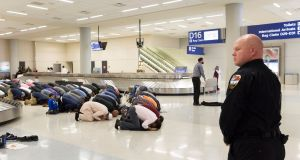 People pray in Dallas/Fort Worth International Airport in protest against the travel ban imposed by President Donald Trump. Photograph: Laura Buckman/Reuters