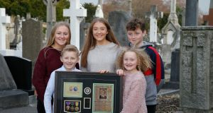 Five great grand nephews of  Michael Walsh at Glasnevin cemetery, Dublin with a display case containing his Purple Heart medal. Photograph: Nick Bradshaw