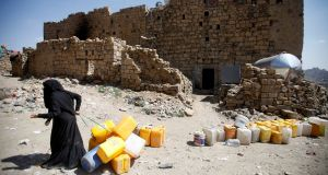 A woman displaced from the Red Sea port city of Hodeidah pulls empty canisters outside her family shelter in Sanaa, Yemen earlier this month. Photograph: Reuters/Mohamed al-Sayaghi