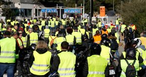 People wearing yellow vests, a symbol of a French drivers' protest against higher fuel prices, block the toll both in Antibes, France. Photograph: Eric Gaillard/Reuters