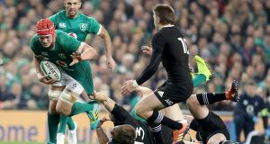 Ireland's Josh van der Flier is dragged back by Beauden Barrett of New Zealand during the Guinness Series Test match at the Aviva Stadium in Dublin. Photo: Dan Sheridan/Inpho