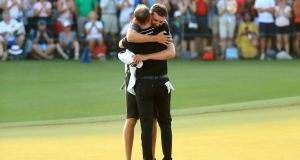 Danny Willett celebrates his victory in Dubai with caddie Sam Haywood. Photograph: Andrew Redington/Getty