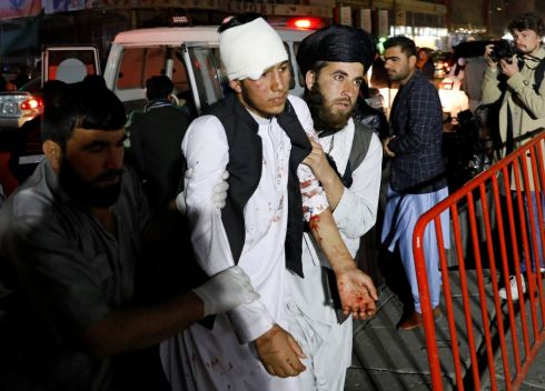 SUICIDE BOMBING: An injured man is assisted into a hospital after a suicide bomb attack in Kabul, Afghanistan, that cost the lives of at least 40 people. Photograph: Mohammad Ismail/Reuters