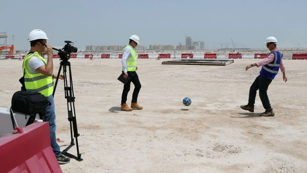 Tamim Loutfi Elabed (R), project manager of the construction of Lusail stadium, the 80,000-seater venue which will host the opening match and the final plays football on the site of the stadium. Photo: Karim Jaafar/Getty Images