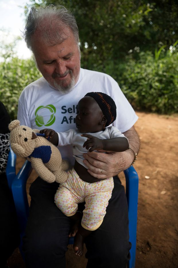 Ronan Scully with baby Joseph in Kiyumo in Eastern Uganda with a present of a teddy bear called Philly, one of many gifts from children from schools in Ireland.