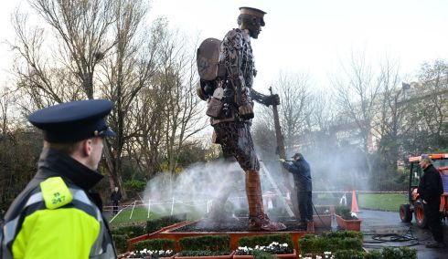 VANDALISM: A Garda stands on duty during the cleaning of the Haunting Soldier sculpture in St. Stephens Green, Dublin following its vandalism overnight. Photograph: Dara Mac Donaill/The Irish Times