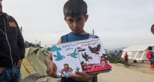 "A Syrian boy in a refugee camp in Greecve with his  painting book. The writing on the left says ""Europe the land of peace and love"" and on the right ""Syria the land of monsters"""