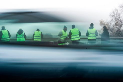 "SPENDING PROTEST: Protestors stand on a bridge over the N70 road on November 23rd, near Montceau-les-Mines, central France, as part of nationwide movement called the Yellow Vests (Gilets Jaunes in French) against high fuel prices which has mushroomed into a widespread protest against stagnant spending power. - A national gathering of the ""Yellow Vests"" is scheduled in Paris on Saturday, November 24th. Photo by Romain Lafabregue/AFP/Getty"