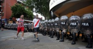 Two River Plate supporters walk past riot police after the Copa Libertadores final  second leg against  Boca Juniors was postponed in Buenos Aires. Photograph: Alberto Raggio/Reuters