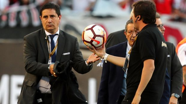 Officials remove the matchball after the match was postponed. Photograph: Marcos Brindicci/Reuters