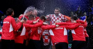 Marin Cilic is mobbed by his Croatia team-mates and coaches after securing the country's second Davis Cup title with a victory over France's Lucas Pouille  in their singles match final in Lille. Photograph: Pascal Rossignol/Reuters