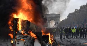 A truck burns during a protest  against rising oil prices and living costs near the Arc of Triomphe on the Champs Élysées  in Paris on Saturday. Photograph: Bertrand Guay/AFP/Getty Images
