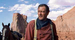 "John Wayne as Ethan Edwards in John Ford's film, The Searchers. ""Ford and Wayne forged an identity for America that lasted for decades."" Photograph: AP/Warner Bros"