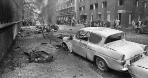 One of the 26 killed by the Dublin bombings in May 1974 lies covered on the path on South Leinster Street (Nassau Street) on Dublin while the bombed car smoulders in the background. Photograph: Tom Lawlor