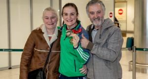 World champion Kellie Harrington shows off her gold medal alongside her parents  Yvonne and Christy on her return to Dublin airport on Sunday. Photograph: Morgan Treacy/Inpho