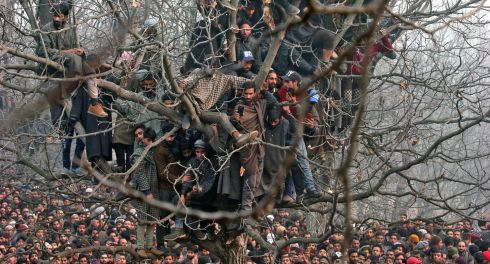 WAITING: People sit in a tree as they wait to offer funeral prayers for Mohd Waseem Wagay, a suspected militant, who according to local media was killed in a gun battle with Indian security forces, at Amshipora village in south Kashmir's Shopian district on November 25th. Photograph: Danish Ismail/Reuters
