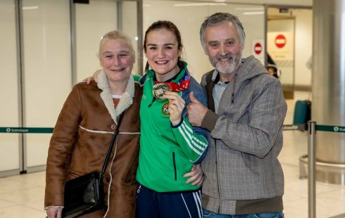 CHAMPION'S RETURN: World champion Kellie Harrington shows off her gold medal alongside her parents Yvonne and Christy on her return to Dublin airport on Sunday. Photograph: Morgan Treacy/Inpho