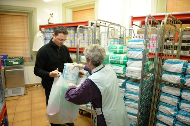 Anne Nolan and Anderson Cassio at work in the Capuchin Day Centre where they distribute baby supplies. Photograph: Dara MacDónaill/The Irish Times