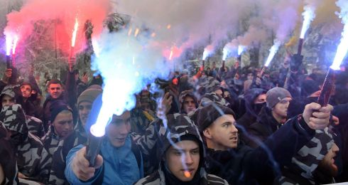Activists of Ukrainian far-right groups hold flares during their rally in front of the Ukrainian parliament in Kiev. They are demanding imposition of martial law in the country and severing diplomatic relations with Russia. Photograph: Sergei Supinsky/AFP/Getty Images