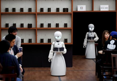 Remotely controlled robots OriHime-D, developed by Ory Lab serve customers at a cafe in Tokyo. Photograph: Issei Kato/Reuters