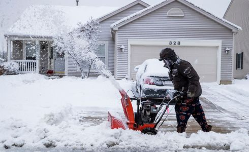 26/11/18: A man uses a snow blower to clear his driveway after a winter storm dumped nearly a foot of snow in Round Lake, Illinois, United States. Photograph: EPA/TANNEN MAURY