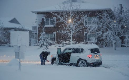 A woman clears snow from around her car during a snowstorm in Arlington Heights, Illinois, United States. Photograph: REUTERS/Kamil Krzaczynski