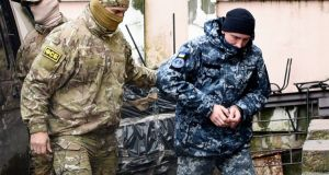 A Ukrainian sailor (right) is escorted by a Russian intelligence agency FSB officer to a courtroom in Simferopol, Crimea on  Tuesday. Photograph: AP Photo