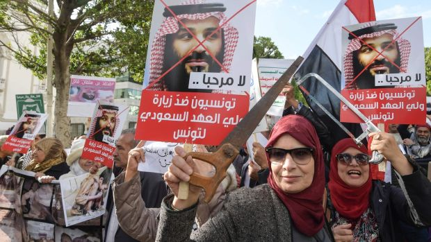 "Tunisian women hold up saws and signs showing pictures of Saudi Crown Prince Mohammed bin Salman with a caption below reading in Arabic ""no welcome, Tunisians against the visit of the Saudi Crown Prince to Tunisia"", during an anti-Saudi Crown Prince protest in the capital, Tunis on November 27th Photograph: Fethi Belaid/ AFP/Getty"
