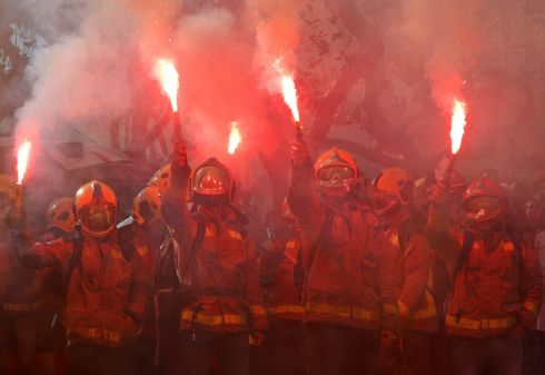 BARCELONA FLARES: Firemen raise up flares during a protest against cuts and working conditions in front of the Catalonia Parliament in Barcelona, Spain on November 28th. Photograph: Albert Gea/Reuters