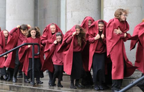 TAKING COVER: Boys and girls from the Piccolo Lasso choir head inside the National Concert Hall yesterday after a photocall for the ESB Grand Christmas Concert. Photograph: Nick Bradshaw
