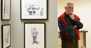 Martyn Turner stands by examples of his work on display at CHQ in Dublin Photograph: Dave Meehan/The Irish Times