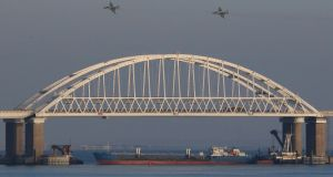 Russian jet fighters fly over a bridge connecting the Russian mainland with the Crimean peninsula with a cargo ship beneath it after three Ukrainian navy vessels were stopped by Russia from entering the Sea of Azov via the Kerch Strait in the Black Sea. File photograph: Pavel Rebrov/Reuters