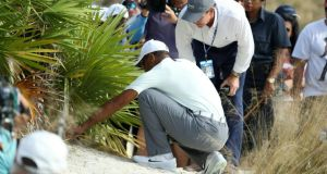 Tiger Woods escaped a penalty after a double-hit while trying to remove his ball from under a bush on the 18th. Photograph: Rob Carr/Getty