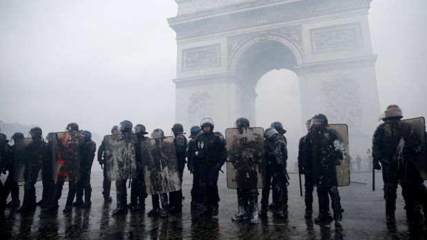 French riot police stand guard at the Arc de Triomphe during clashes with protesters wearing yellow vests at the Place de l'Etoile in Paris, France. Photograph: Stephane Mahe/Reuters