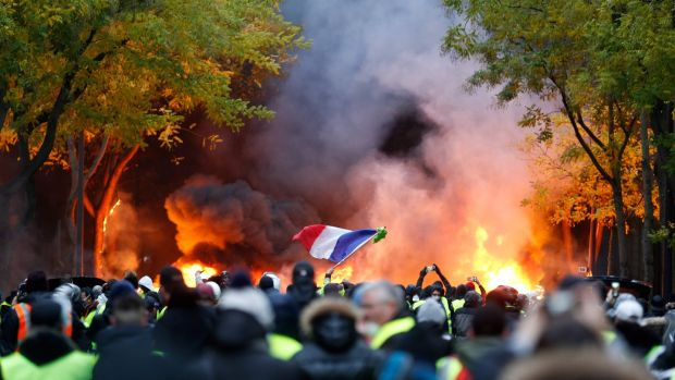A French flag is seen as fires burn during a protest of yellow vests (gilets jaunes) against rising oil prices and living costs, on in Paris on Saturday. Photograph: Getty